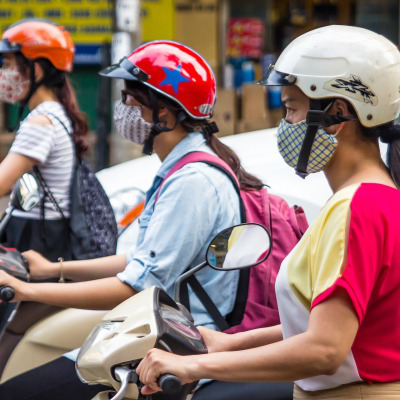 Three girls on scooters wearing helmets and masks